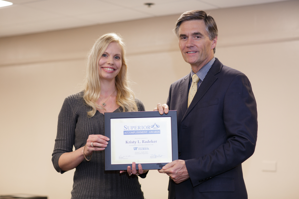 Kristy L. Radeker presented with her UF Superior Accomplishment Award by College of Medicine Dean, Dr. Michael L. Good.