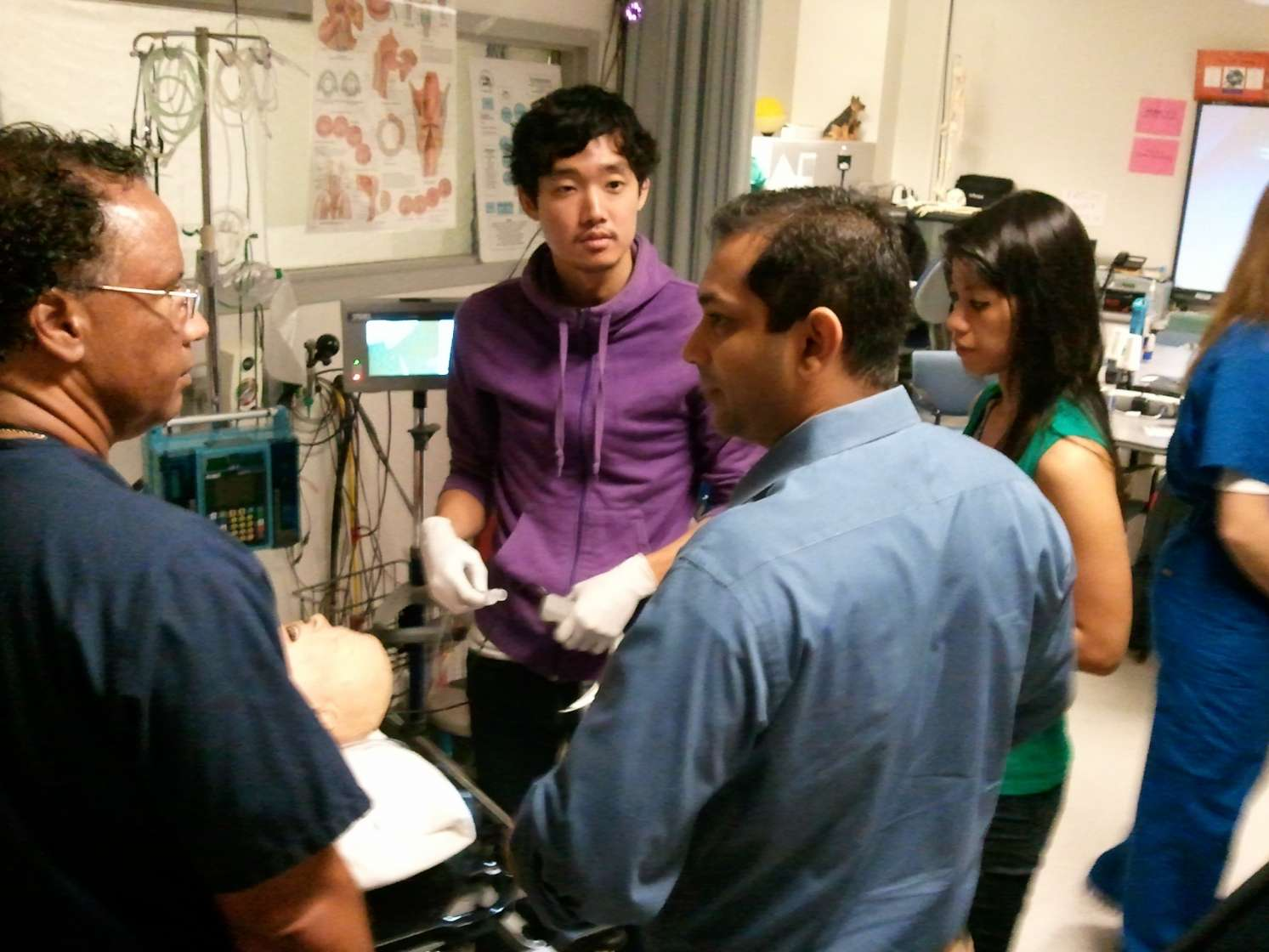 Students and teachers around a medical device.