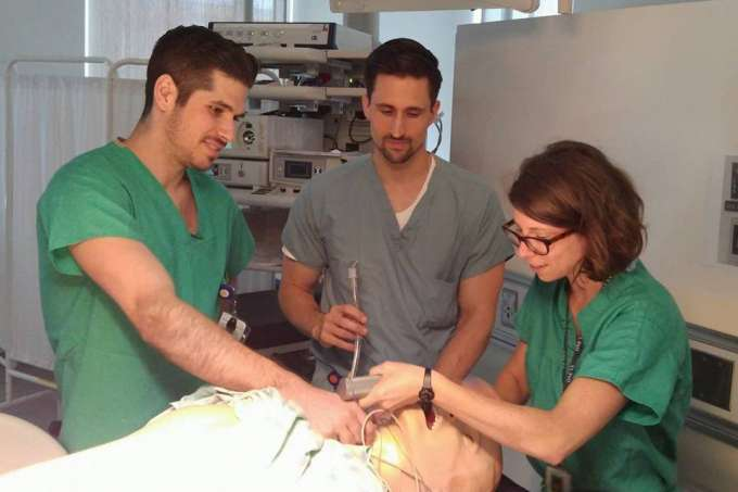 Students in the clerkship work perform a procedure on a medical simulator.