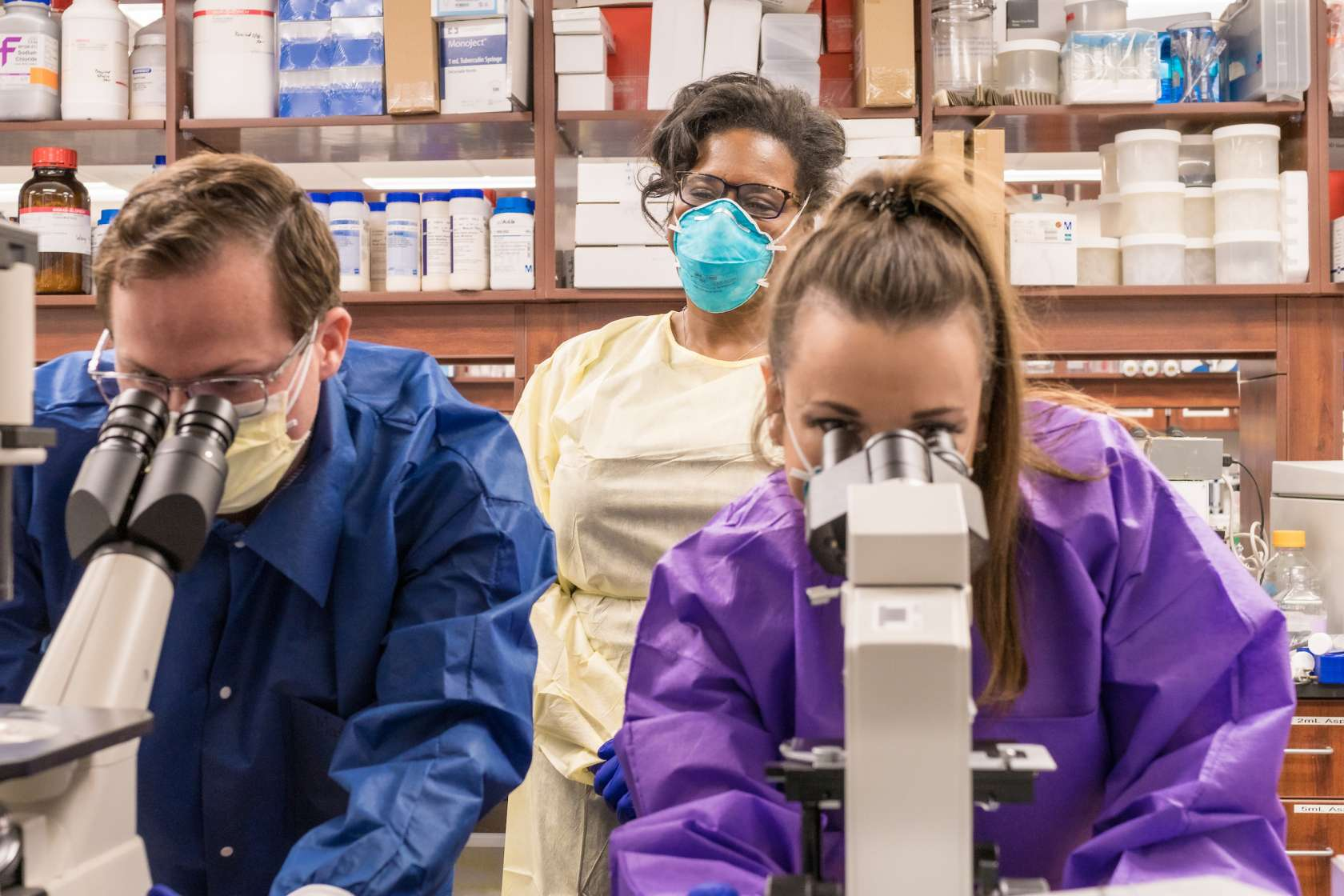 Two students look into microscopes while a female researcher watches them from behind.